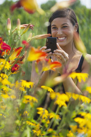 Cute Asian woman smiles while taking pictures of flowers with a small camera. Vertical shot. Stock Photo