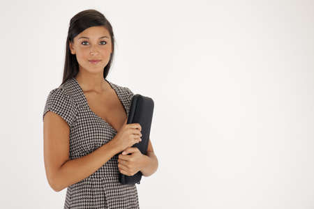 Beautiful young Asian woman smiles at the camera while holding a laptop case in her arms. Horizontals shot.