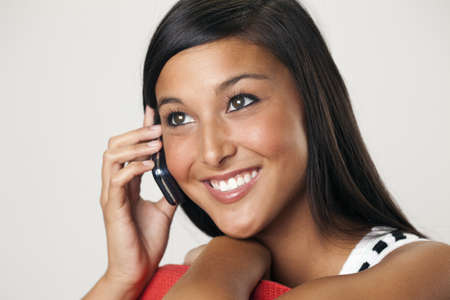 Attractive young Asian woman smiles while holding a mobile phone to her ear. Horizontal shot.