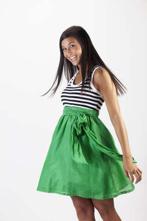 Beautiful young Asian woman models a green skirt. She is smiling towards the camera and has her hair in motion. Vertical shot. Stock Photo