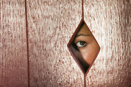 Woman peeks through a diamond shaped hole in a wall. Horizontal shot.