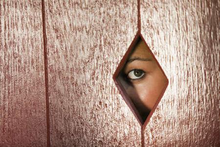 diamond shaped: Woman peeks through a diamond shaped hole in a wall. Horizontal shot.
