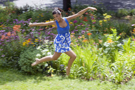 Beautiful young woman leaps on a grass lawn with bushes and flowers in the background. She is smiling at the camera. Horizontal shot.