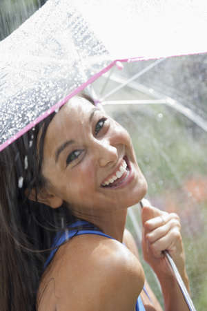 Beautiful young woman smiles towards the camera while holding an umbrella under a spray of water. Vertical shot. Stock Photo