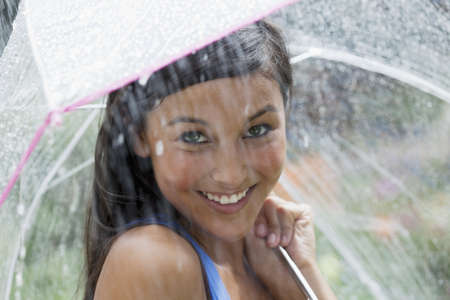 Beautiful young woman smiles towards the camera while holding an umbrella under a spray of water. Horizontal shot. Stock Photo