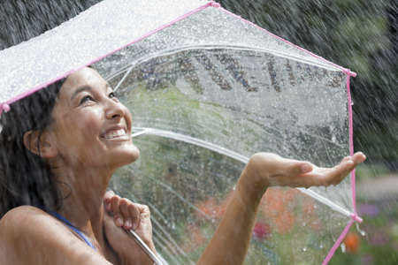 umbrella rain: Beautiful young woman grins as she holds out her palm to catch falling water. She is holding an umbrella over her head. Horizontal shot.
