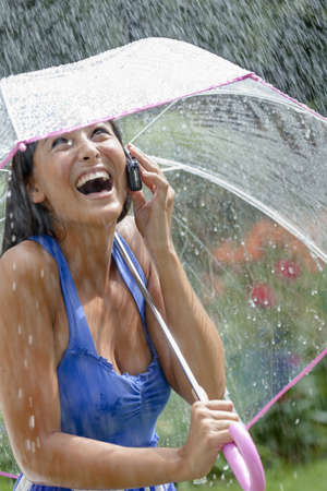 Attractive young woman laughs while talking in the phone in a rainstorm. She is holding a clear umbrella over her head. Vertical shot. Stock Photo