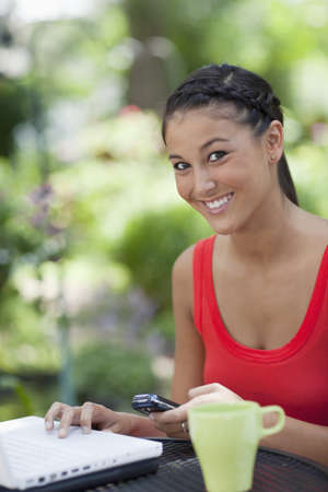 Young Asian woman sits at an outdoor mesh table with a laptop, mobile phone and coffee cup. She is smiling at the camera. Vertical shot.