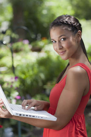 Beautiful young Asian woman smiles at the camera while holding a laptop. She is standing outdoors with a garden in the background. Vertical shot.