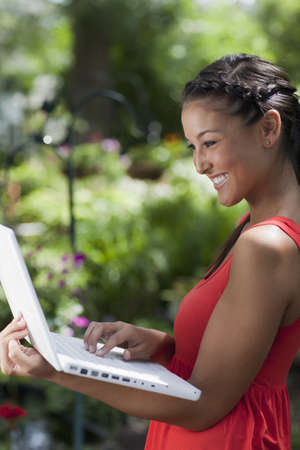 Attractive young Asian woman smiles while typing on a laptop in her arms. She is standing outdoors with a garden in the background. Vertical shot.