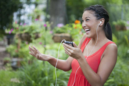 Attractive young Asian woman playfully dances to music on her portable music device. Horizontal shot.