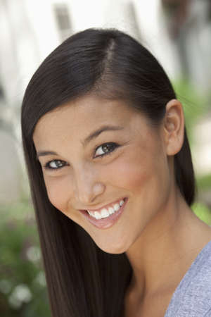 Portrait of a beautiful Asian woman smiling into the camera in an outdoor setting. Vertical shot. photo