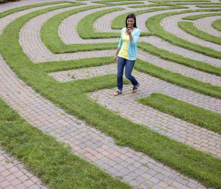 Beautiful young Asian woman smiles while reading her mobile phone and walking through a maze. Square shot.