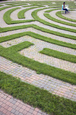 Young woman sits on a bench located in the center of a cobblestone and grass maze. She is working on her laptop. Vertical shot.