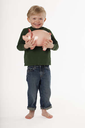 A young, barefoot boy is standing and smiling while holding a piggy bank. Vertical shot. photo