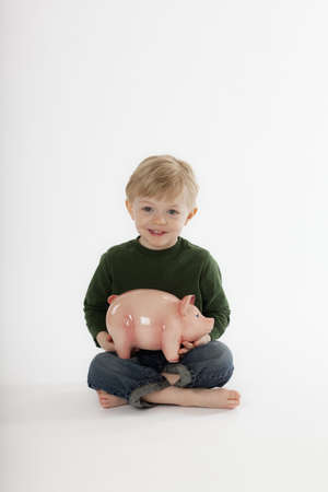 Cute little boy sits cross-legged on the floor while holding a piggy bank. He is smiling towards the camera. Vertical shot. Stock Photo