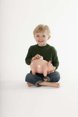 Cute little boy sits cross-legged on the floor and smiles at the camera while inserting a coin into a piggy bank. Vertical shot.