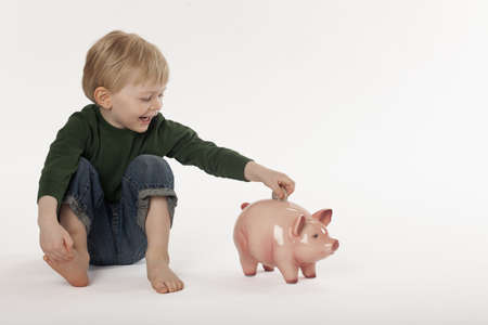 Cute little boy puts a coin into a piggy bank while sitting on the floor. Horizontal shot.