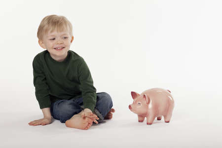 Cute little boy sits cross-legged next to a piggy bank on the floor. Horizontal shot.