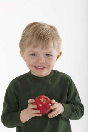 Little boy smiles at the camera while holding an apple in his hands. Vertical shot. Stock Photo