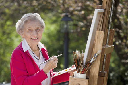 adult only: A smiling senior woman is in an outdoor setting painting. Horizontal shot.