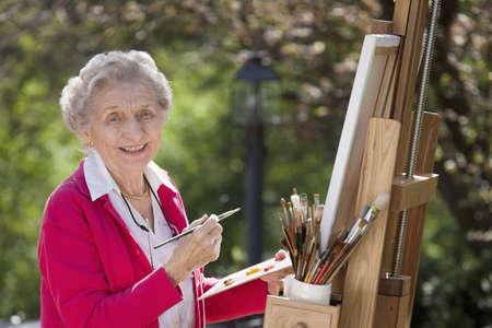 A smiling senior Woman ist ein outdoor-Einstellung-Malerei. Horizontale erschossen. Standard-Bild