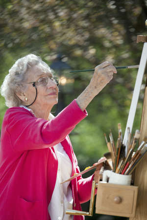only one senior: A smiling senior woman is in an outdoor setting painting. Vertical shot.