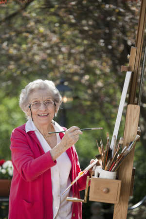 A smiling senior woman is in an outdoor setting painting. Vertical shot.