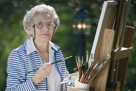 only one senior: A smiling senior woman is in an outdoor setting painting. Horizontal shot.