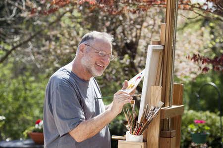 hombre pintando: Hombre pinta sobre un caballete en un agradable entorno al aire libre.  Foto de archivo