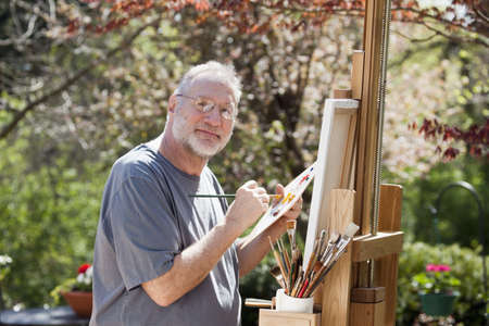 Man paints on an easel in a pleasant outdoor setting.