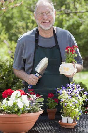 鉢植えの植物を屋外でガーデニングながらカメラで男笑顔。