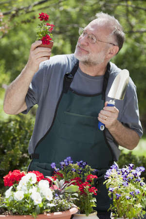Man smiles while gardening with potted plants outdoors. photo