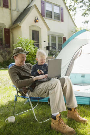 Father and son camping in the front yard with laptop computer