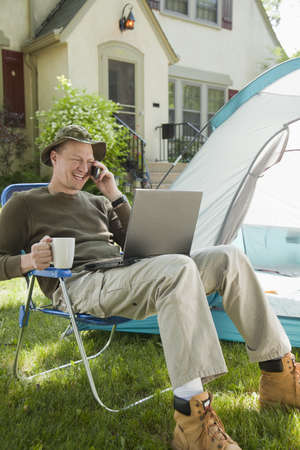 staycation: Man camping in his front yard with laptop computer and cell phone