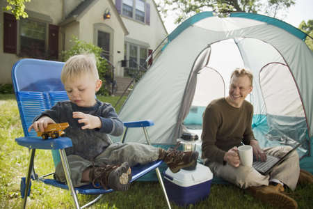 Father with laptop and son playing while camping in the front yard