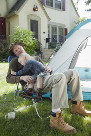 staycation: Father sleeping with son in his lap while camping in the front yard  Stock Photo