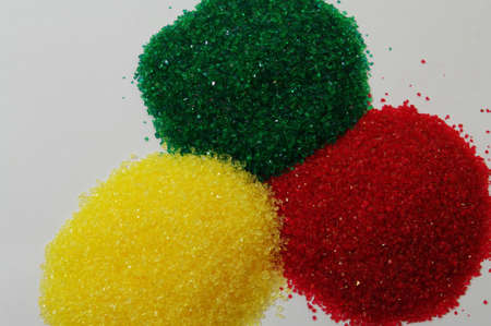 Red, green and yellow crystal sugar in piles photo