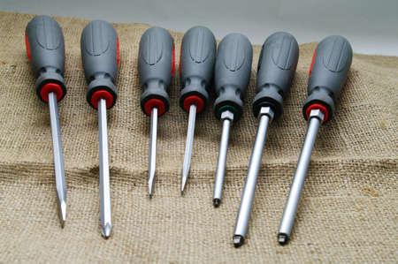 A screwdriver set on a burlap background