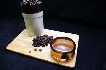 Coffee beans and a grinder on a wooden tray