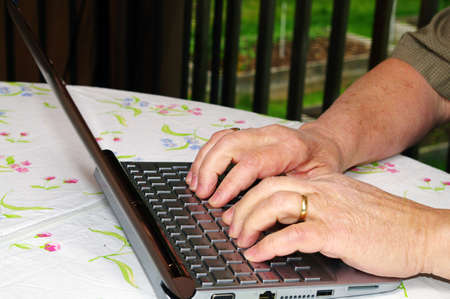 compiler: A man working on a netbook on the deck on a summer day Stock Photo