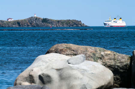 Ferry entering port  around the Swallow Tail Lighthouse on Grand Maman photo