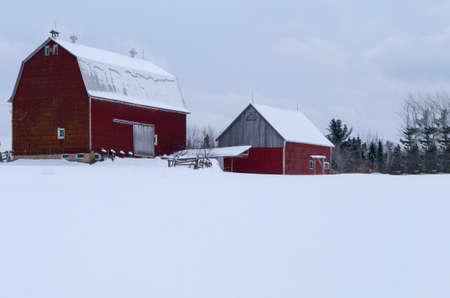 barns winter: Red Barn in the winter in New Brunswick Stock Photo