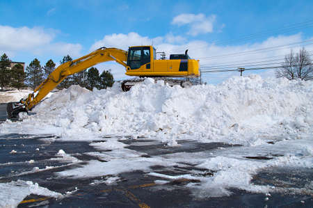 clearing: Excavator clearing snow in a parking lot Stock Photo