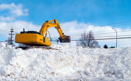 snow clearing: Excavator clearing snow in a parking lot Stock Photo