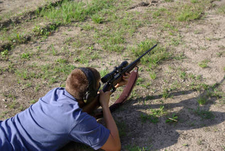 Firing a 30-06 rifle view along rifle on a rifle range in the prone position