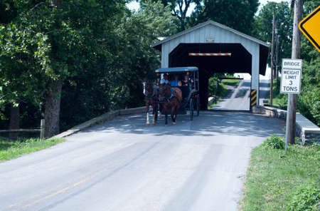 Amish wagon crossing a covered bridge