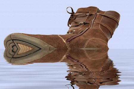 one feminine boot omitted in water lying sole onward, on background color paper Imagens