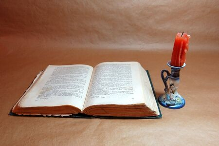 old open book and candle on paper background photo