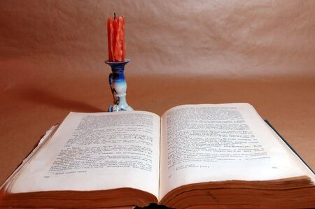 old open book with candle on paper background photo